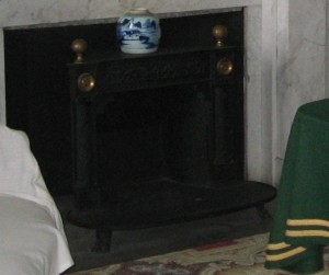 An iron Franklin style stove inserted into a white marble fireplace.