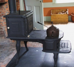 Stepped iron cookstove in front of a fireplace seen from the side