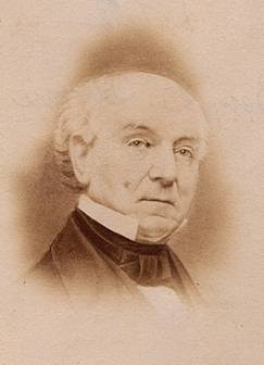 A sepia-toned portrait of the head and shoulders of an older, white haired, balding man wearing a cravat and high collar.