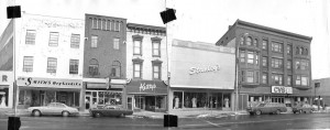 Two photos of buildings taped together. Shows 1970s cars parked out front of JW Smith's, Keilty's, Stanley's and CVS.
