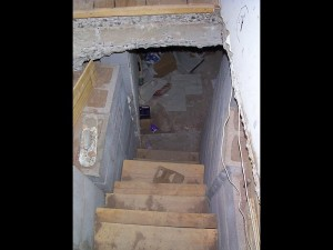 Old stairs leading to a messy basement floor.
