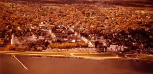 Airborne view of a city on a lakefront showing many buildings and trees, as well as a divided highway along the lakeshore.