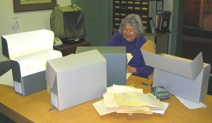 woman sitting behind a long table with several boxes in front of her