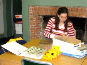 Woman sitting at a table with boxes of slides and a binder to put them in.