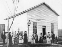 A group of mostly black men and women wearing shawls and hats stand on a sidewalk outside a white clapboard building with a lampost.