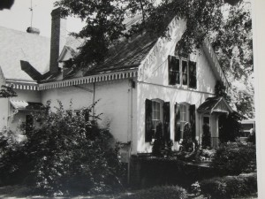 Black and white image of a Gothic style house with two first floor and one second floor window visible on the front.