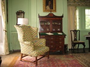 Light green painted room with antique furniture and needle pointed wing chair.