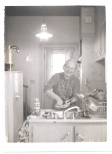 A woman washing dishes in a 1950s kitchen.