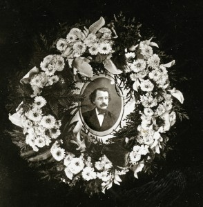 A black and white portrait of a man with a mustach and beard dressed in a suit and cravat. The image is surrounded by a wreath of arbor vitae, ferns and flowers.