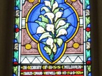 A stained glass window with lilies and the names and death dates of 10 Sunday School children who died of diphtheria.