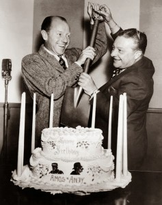 """Two men in suits pretend to cut a 2-layer cake with a garden spade. The cake is surrounded by nine tapered candles and has """"Happy Birthday Amos n Andy"""" on it in frosting along with the images of two black men."""