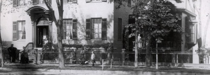 A man, woman and five girls stand in front of the Prouty-Chew House. One girl stands on a side porch and another on the front stoop.