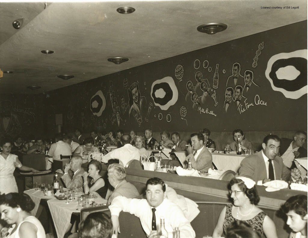 People sitting at tables and in booths at a club. The wall is decorated with the drawings of performers like the Four Aces and the Mills Brothers.