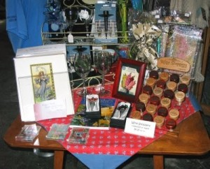 A display on a table of framed prints, wooden wine bottle stoppers and magnets.