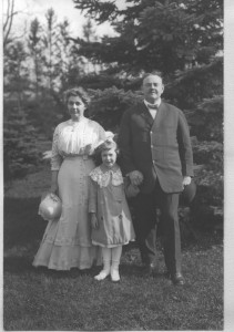 woman, little girl, and man standing outside in front a tree