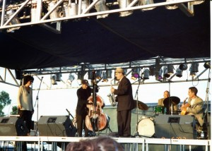 Colored photo of five musicians performing on an outdoor stage.
