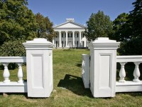 Looking at an elegant 6-columned Greek revival house across an expanse of lawn from just outside a low white gate.