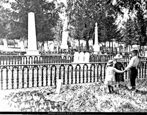 Black and white photo of three children playing in Washington Street Cemetery