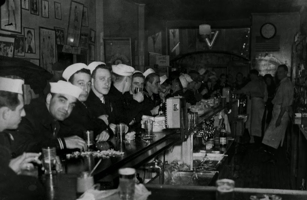 Sailors lined up along a bar.