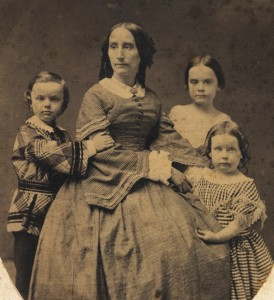woman-seated-surrounded-by-3-children