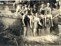 Girls in 1920s bathing suits and caps sitting on the edge of a small waterfall.