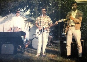 Colored photo of three members of the Tokens. Three men are playing musical instruments outside