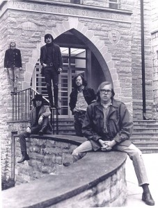 Black and and white image of the band Lost and Found. Members of the band are posed outside of a building