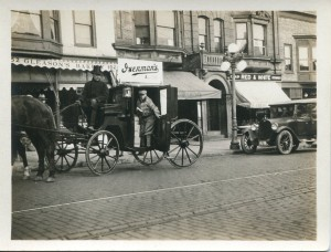 Black and white photography of a horse drawn delivery service carriage