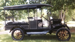 Colored photo of a 1916 Model T ford Canopy Express underneath a tree.