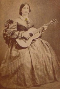 Sepia colored photograph of a young woman with a parlor guiltar