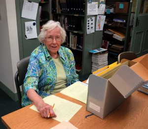 Colored photograph of an elderly woman working at a table in a research room