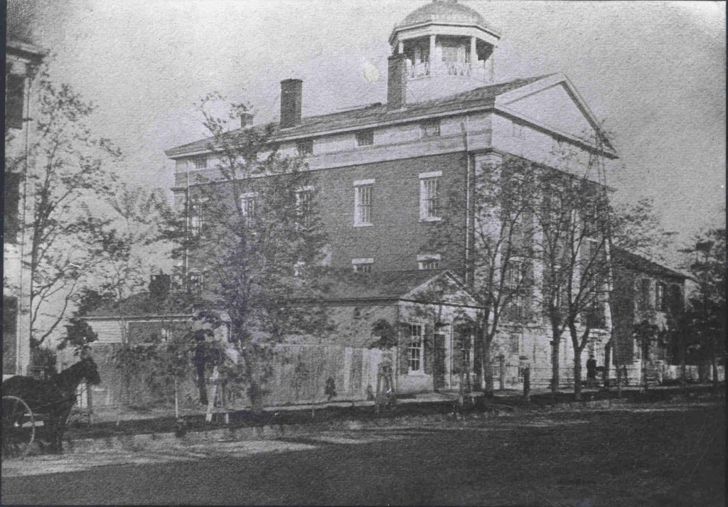 Street view of a large brick building with white columns and a rounded cupola at the top.