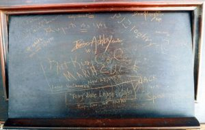 Music holder from the front piece of an upright piano with signatures from musicians who played at Club 86 in the 1940s and 1950s. Nat King Cole's signature is in the middle.