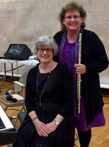 Woman holding a flute and standing behind a woman seated at a piano