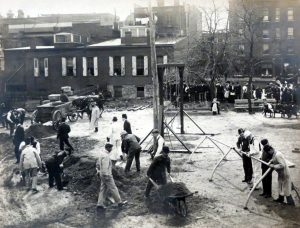 men building a playground with people watching