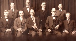 group of gentlemen sitting and standing