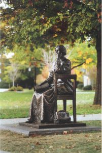 statue of a woman sitting in a chair with a bag at her feet