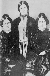one young lady standing between two seated ladies