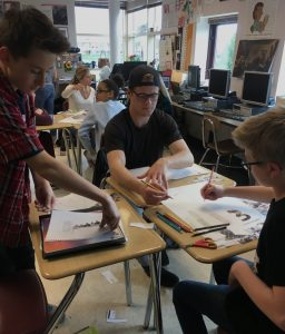 three-students-in-classroom-pasting-items-on-paper