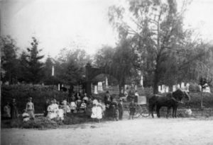 group of people with a horse and carriage standing outside a cemetery