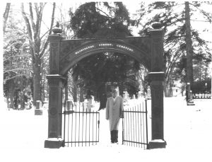 man standing under an arch in the snow