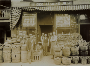 Group of men standing outside a store surrounded by baskets of produce