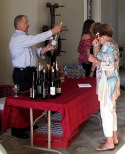 man serving wine to a woman