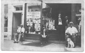 men standing and sitting outside a store front