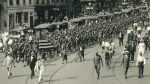 Parade of men in army uniforms accompanied by civilians walking and biking on road with trolley tracks.