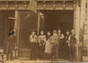 men and women standing outside an office
