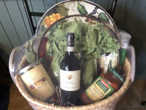 Basket filled with jars, wine, and plates