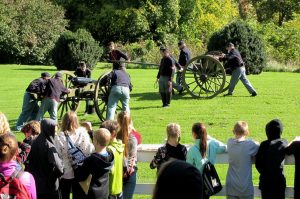 Civil War re-enactors loading cannons with children watching from behind a fence