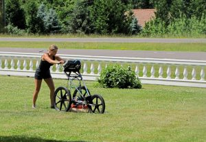 girl pushing a machine in a front yard