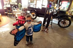 little boy wearing toy butterfly wings with a car in the background